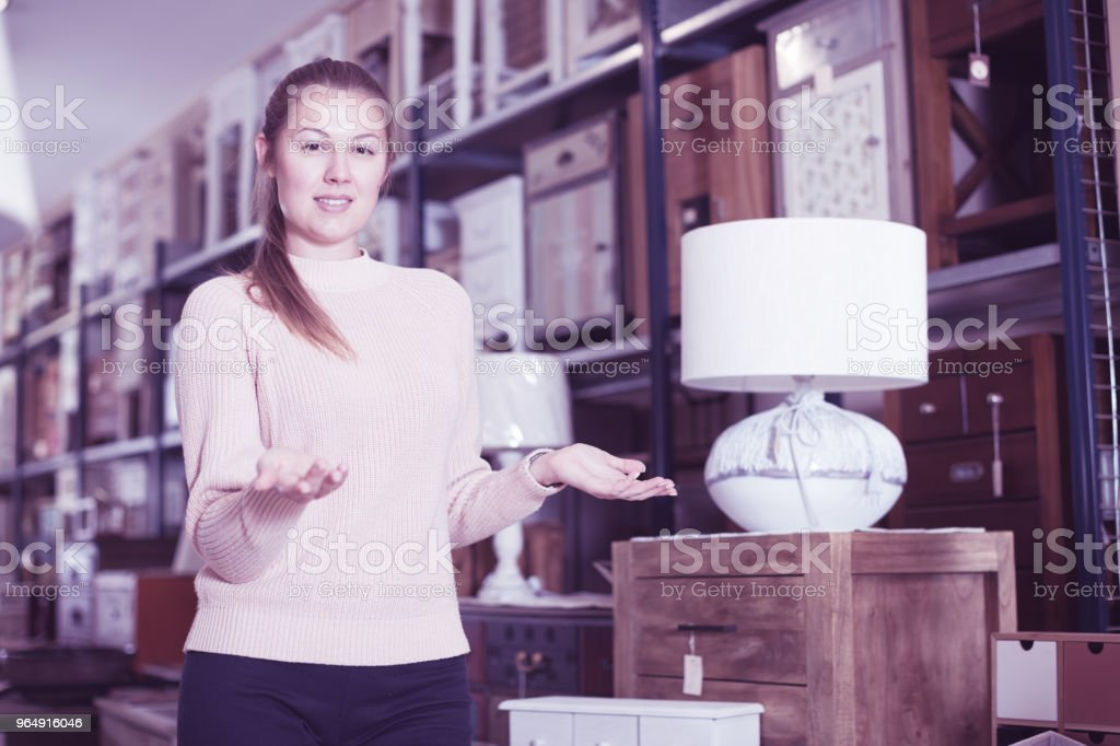 Adult woman consumer near chest of drawers royalty-free stock photo