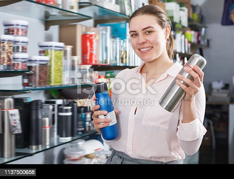 Adult woman consumer with thermos in the tableware shop
