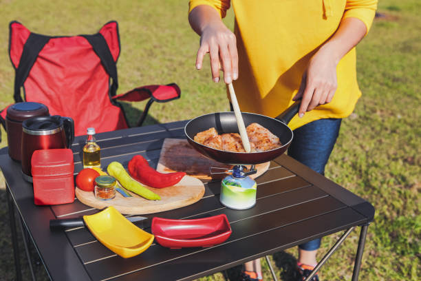 Adult Woman Cooking a Meal in Nature Adult Woman Cooking a Meal in Nature foldable stock pictures, royalty-free photos & images