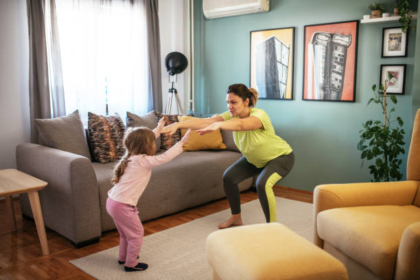 Adult woman dancing at home during quarantine with three year old daughter stock photo