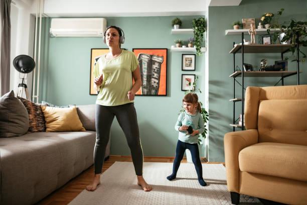 mulher adulta dançando em casa durante quarentena com filha de três anos - dançar - fotografias e filmes do acervo