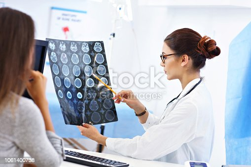 865688550 istock photo Adult woman discussing x-ray results during visit at female doctor's office 1061400738