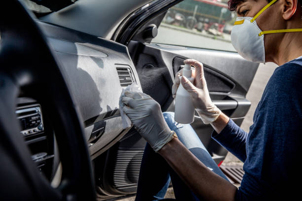 Adult Woman Disinfecting Car Dash Board with Antiseptic and Wet Wipe - stock photo Adult Woman Disinfecting Car Dash Board with Antiseptic and Wet Wipe decontamination stock pictures, royalty-free photos & images