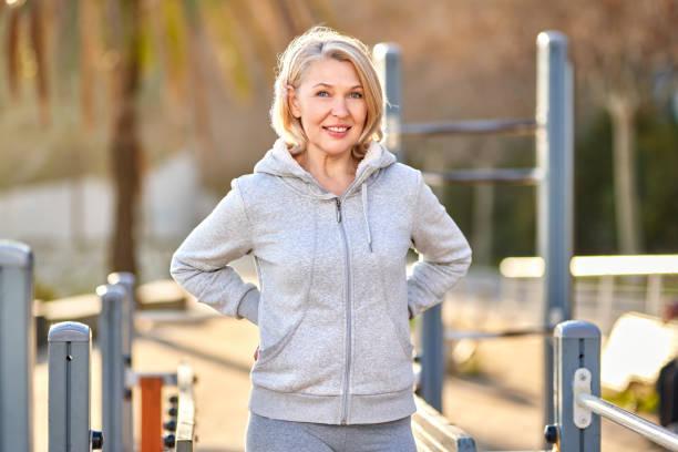 Mujer adulta haciendo ejercicio en el parque. Concepto deportivo y de estilo de vida activo. - foto de stock