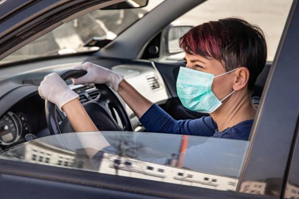 Erwachsene Frau fahren zur Arbeit tragen N95 Gesichtsmaske und chirurgische Handschuhe während COVID-19 Ausbruch - Stockfoto – Foto