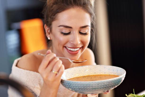 adult woman eating pumpkin soup in the kitchen - sopa imagens e fotografias de stock