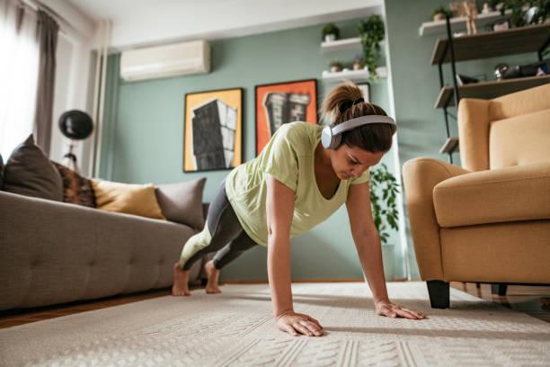 Adult woman exercising at home during quarantine, doing push ups stock photo