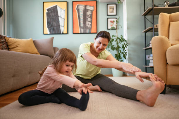 Adult woman exercising at home during quarantine stock photo