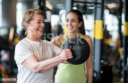 Adult woman exercising at the gym with a personal trainer and looking very happy - healthy lifestyle concepts
