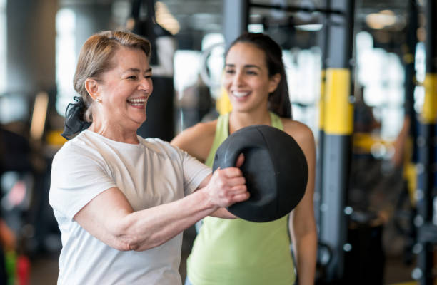Adult woman exercising at the gym with a personal trainer stock photo