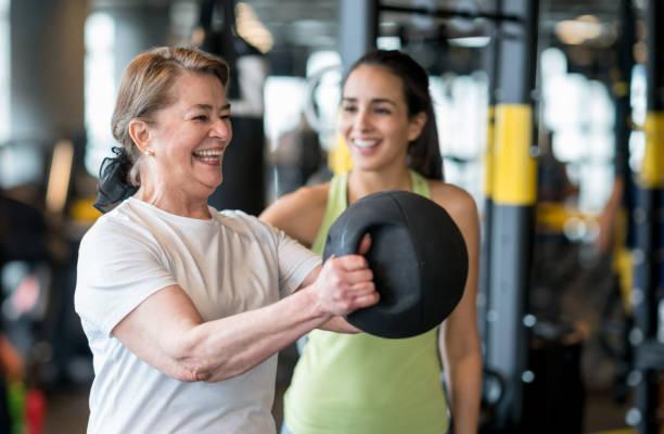 mujer haciendo ejercicio en el gimnasio con un entrenador personal - entrenador personal fotografías e imágenes de stock