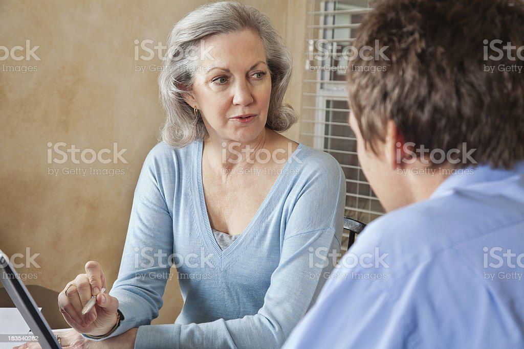 Adult Woman Explaining Something on Computer to Couple royalty-free stock photo