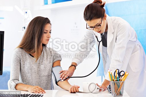 istock Adult woman having blood pressure test during visit at female doctor's office 1061399292