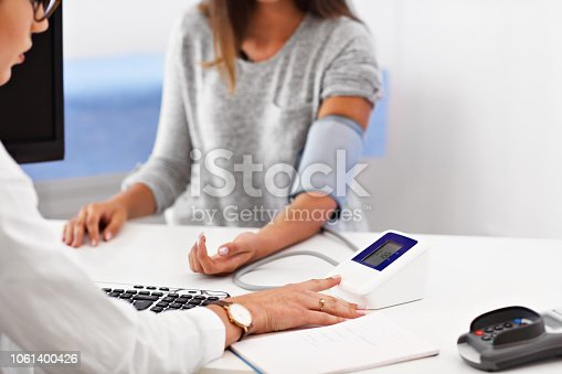 istock Adult woman having blood pressure test during visit at female doctor's office 1061400426