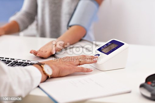 istock Adult woman having blood pressure test during visit at female doctor's office 1061400436