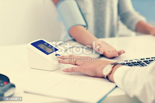 istock Adult woman having blood pressure test during visit at female doctor's office 1061400614
