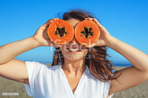 istock Adult woman hold in hands ripe fruit - orange papaya 530432056