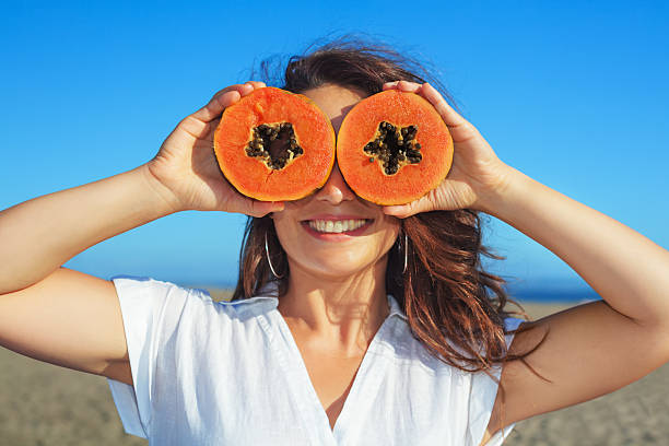 adult woman hold in hands ripe fruit - orange papaya - funny fat lady stock photos and pictures