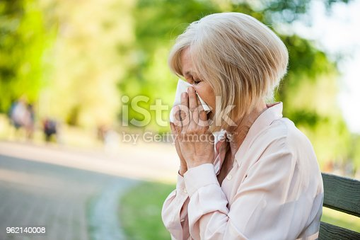 Adult woman is sitting in park and blowing nose. She is having allergy.
