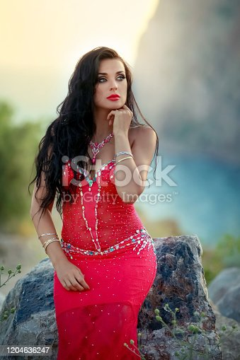 1054970060 istock photo Adult woman in red dress outdors 1204636247