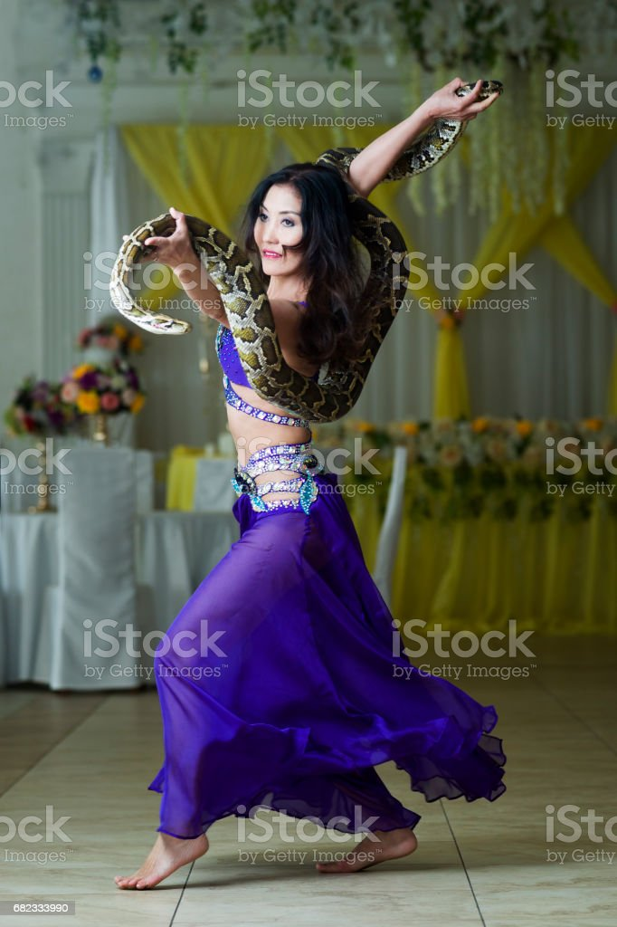 Adult woman in stage costume performs with big snake foto stock royalty-free