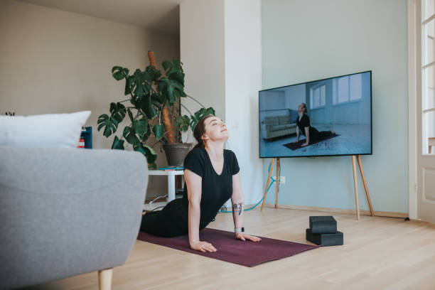 Adult woman in upward facing dog position during online yoga lessons Photo series of stay-at-home fitness during lockdown in self isolation. upward facing dog position stock pictures, royalty-free photos & images