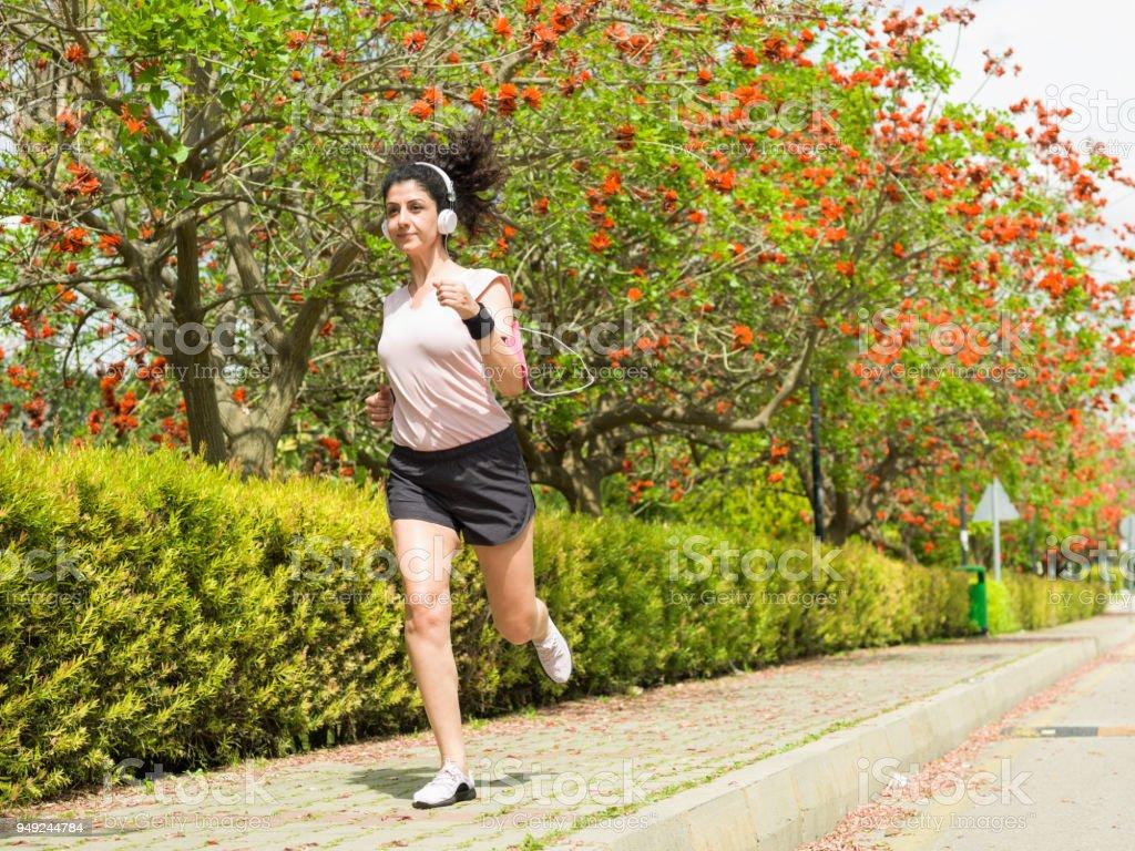 Femme adulte Jogging dans le parc Public de la ville au printemps photo  libre de droits 3e833c1f643