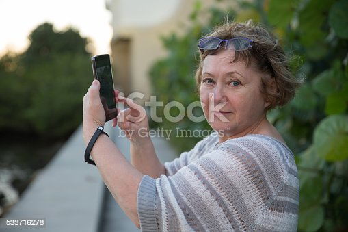 Pretty adult woman photographing by telephone looking at camera
