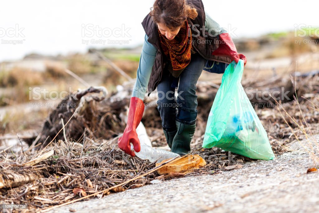 Adult Woman Picking Up Trash in Rural Scene Adult Woman Picking Up Trash in Rural Scene. Adult Stock Photo