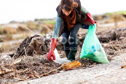 Adult Woman Picking Up Trash in Rural Scene.