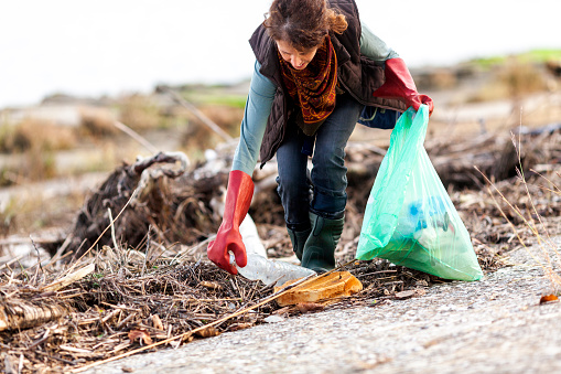 Adult Woman Picking Up Trash In Rural Scene Stock Photo - Download Image Now