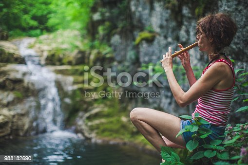 istock Adult Woman Playing on a Whistle Above a Creek 988182690