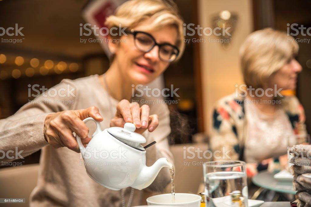 大人女性がカップにお茶を注ぐ ストックフォト