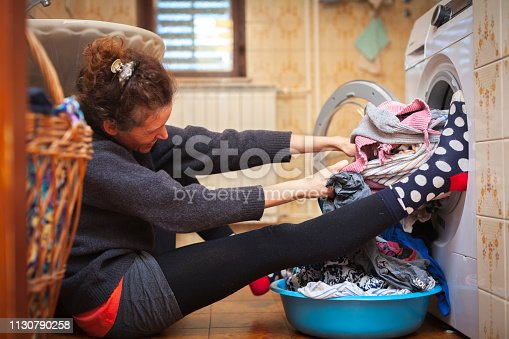 Adult Woman Pulling Stuck Clothes Out of Washing Machine.