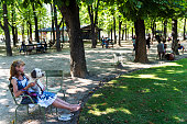 Adult woman resting with dog in her lap at Le Jardin du Luxembourg, Paris, France
