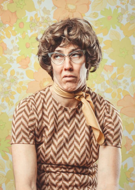 Adult Woman Retro Seventies Style A portrait of a woman in 1970's style, posing in front of a vintage floral wallpaper background.  She has a look of boredom or disgust on her face. rolling eyes stock pictures, royalty-free photos & images