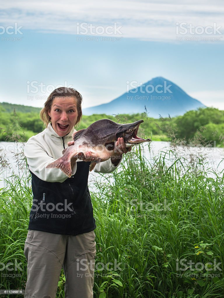 Adult woman screaming joy and holds in hands big fish stock photo