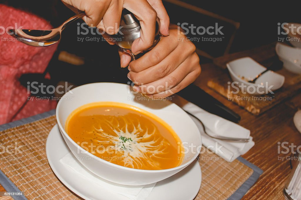 Adult woman seasoning pepper in hot soup stock photo