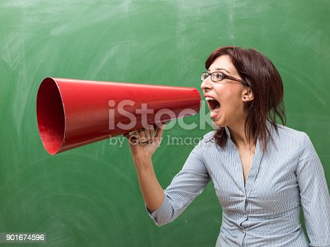 855348688 istock photo Adult Woman Shouting Through Megaphone In Front Of Green Chalkboard 901674596