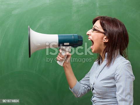 istock Adult Woman Shouting Through Megaphone In Front Of Green Chalkboard 901674604