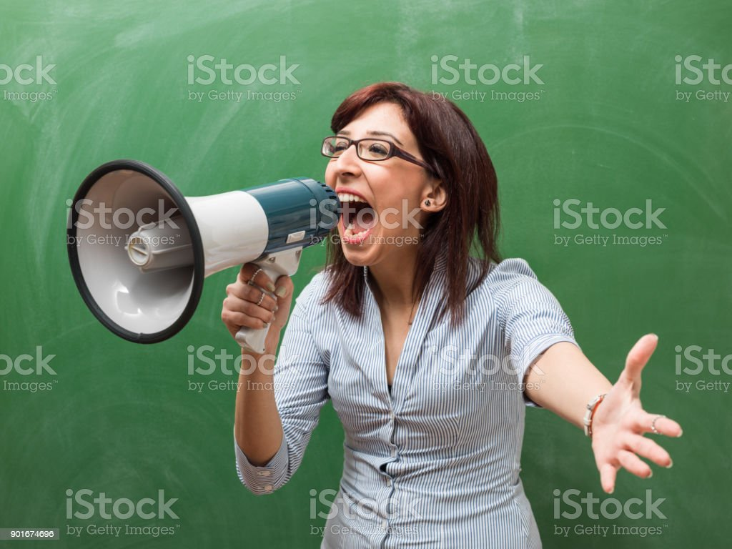 Adult Woman Shouting Through Megaphone In Front Of Green Chalkboard stock photo