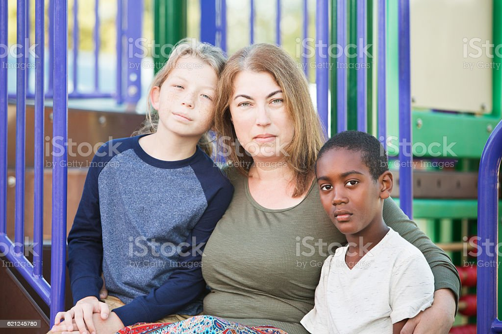 Adult woman sitting with two boys stock photo