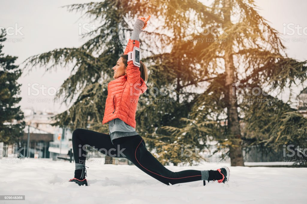 Adult woman stretching in public park stock photo