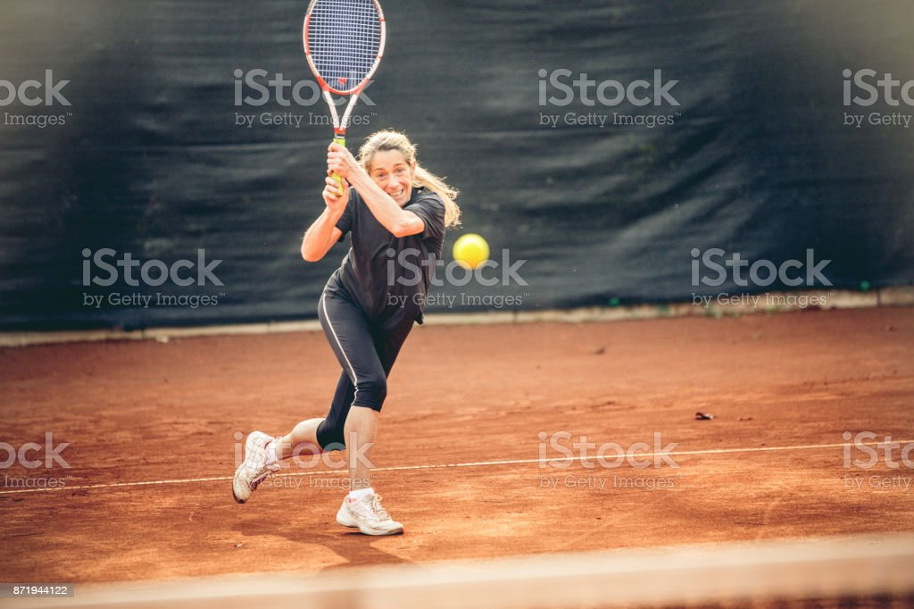 Adult Woman Swinging at the Ball stock photo