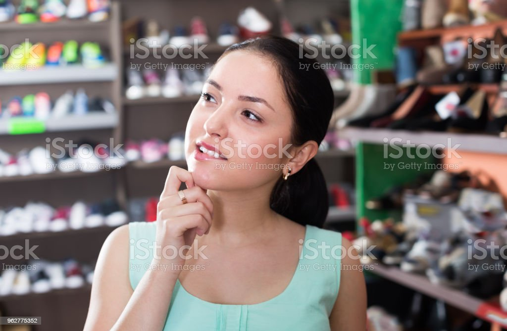 Adult woman that is looking on shelves - Foto stock royalty-free di 25-29 anni