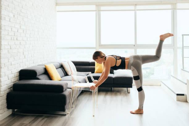 Adult Woman Training Body By Raising Legs Using Chair stock photo