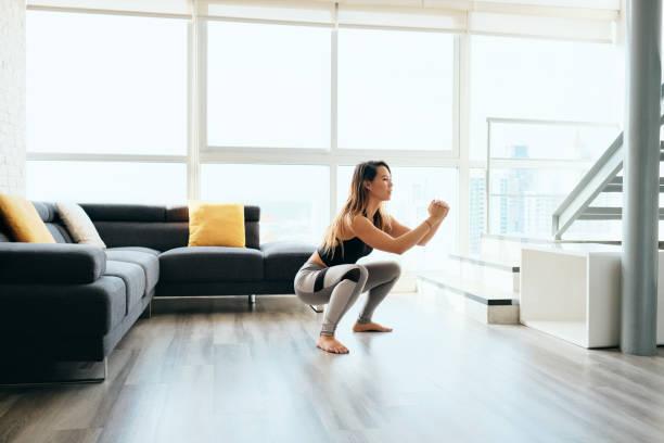 Erwachsene Frau trainiert Beine, die in und aus dem Squat machen – Foto