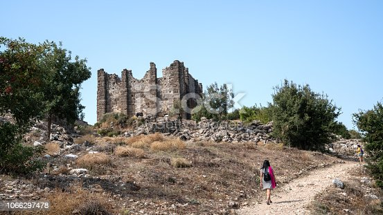 Adult woman walking on dirt pathway in antique city of Aspendos, Antalya, Turkey. Ruins of old basilica is seen on the left side of horizontal frame. Sky is clear and blue. Shot in outdoor with a mirrorless camera.