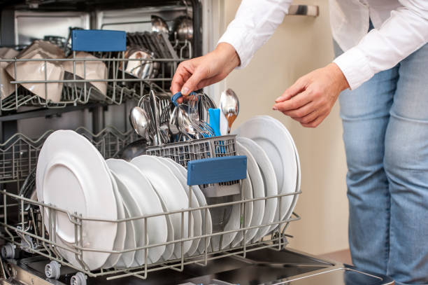 Adult Woman Unloading Dishwasher In The Kitchen Adult Woman Unloading Dishwasher In The Kitchen dishwasher stock pictures, royalty-free photos & images