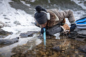 Adult Woman Using Filtrating Drinking Straw To Drink Water From a Lake in Winter.